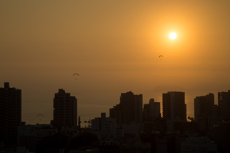 Photograph of paragliders during sunset with the skyline of the district Miraflores in Lima, Peru. Stock Photo