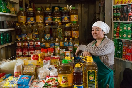 bazar: Osh, Kyrgyzstan - October 5, 2014: A woman selling oil bottles at the bazar in Osh.