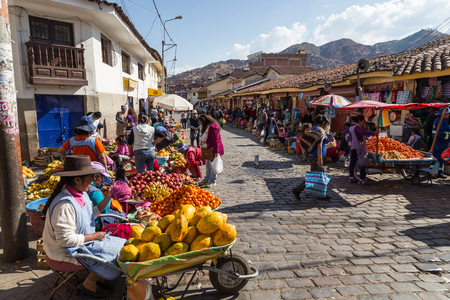 Cusco, Peru - August 08, 2015: People selling and buying fruits at a market in the steets. Editorial