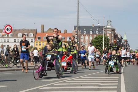 yearly: Copenhagen, Denmark - May 22, 2016: Runners with wheelchairs at the yearly event Copenhagen Marathon.