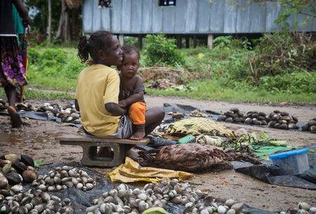 Seghe, Solomon Islands - June 16, 2015: Girl selling mussels and holding baby on the local market. Editorial