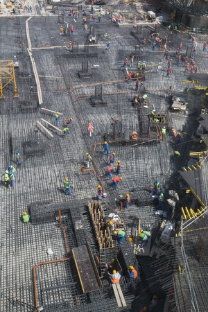 armoring: Dubai, United Arab Emirates - October 16, 2014: Workers preparing steel reinforcement for foundation of a new building.