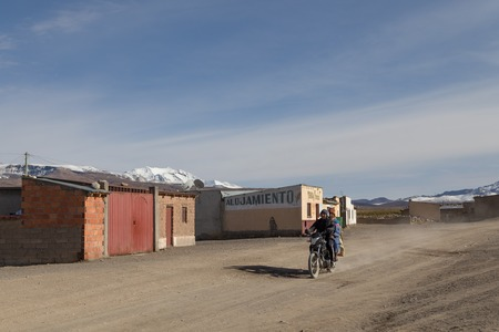 sajama: Sajama, Bolivia - October 27, 2015: Bolivian man and his wife riding a motocycle through the village. Editorial
