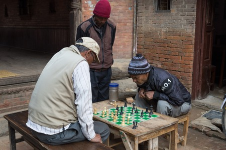 playing the market: Bhaktapur, Nepal - December 5, 2014: Elderly men playing chess in the streets.