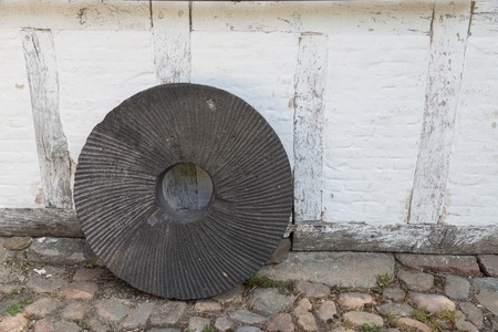 millstone: An old millstone standing on a wall.