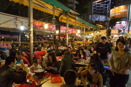 Kaohsiung, Taiwan - January 11, 2015: People having dinner at the night market
