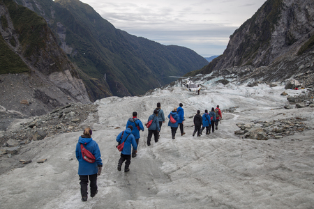 franz josef: Franz Josef, New Zealand - March 22, 2015: A group of tourists hiking towards a helicopter on Franz Josef Glacier.