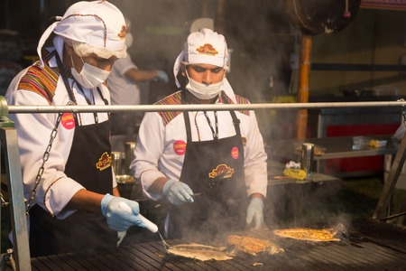 Lima, Peru - September 4, 2015: Two cooks perparing fish at the annual Mistura Food Festival Editorial