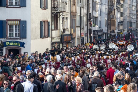 fasnacht: Basel, Switzerland - March 10, 2014: Spectators watching the tradtional carnival parade with dressed up people