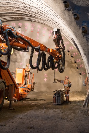 mine site: Geneva, Switzerland - May 22, 2014: Two workers preparing the machine for the construction of piperoof grouting for a tunnel