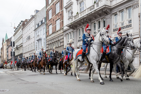 escorting: Copenhagen, Denmark - January 04, 2017: The Guard Hussar Regiment escorting Queen Margrethe in a 24-carat golden coach from Christiansborg Palace to Amalienborg Palace