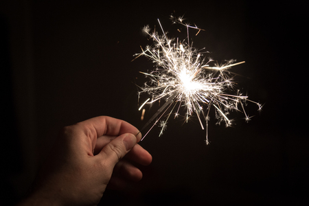 A hand holding a sparkler on a black backgournd