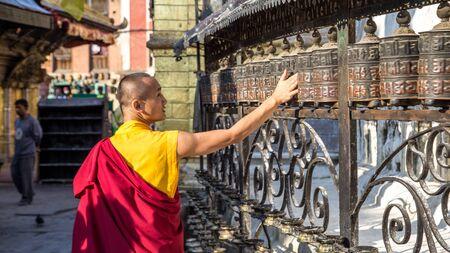 devote: Monk spinning prayer wheels Editorial