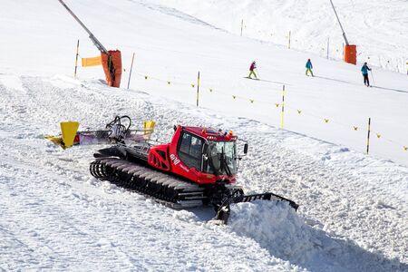 groomer: Snow groomer next to a ski slope
