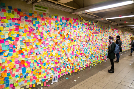 New York, United States of America - November 21, 2016: People looking at sticky post-it notes on wall in Union Square subway station which were set up as protest against presidential election results Editorial