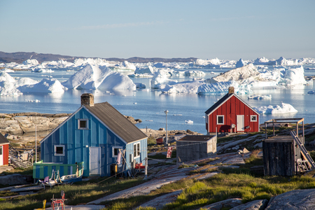 Rodebay, Greenland - July 09, 2018: Colorful wooden houses with icebergs in the background. Rodebay, also known as Oqaatsut is a fishing settlement north of Ilulissat. Sajtókép
