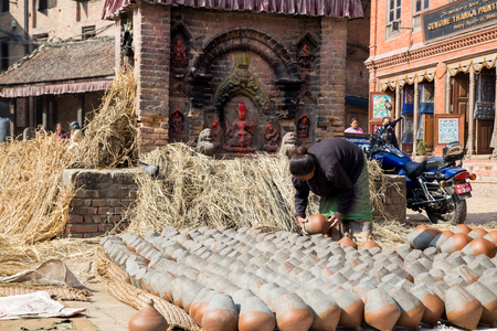 Bhaktapur, Nepal - December 5, 2014: A Nepalese woman sitting next to clay pots on Pottery Square.