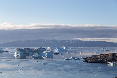 Ilulissat, Greenland - July 9, 2018: The coastline and icebergs during midnight sun. Rodebay, also known as Oqaatsut is a fishing settlement north of Ilulissat.