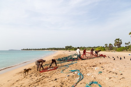 Trincomalee, Sri Lanka - August 20, 2018: Fishermen sorting a big fishing net at Nilaveli Beach Redakční