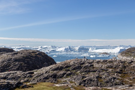 Ilulissat, Greenland - June 30, 2018: An unidentified tourist sitting at the Ilulissat Icefjord viewpoint