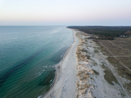 Melby, Denmark - April 18, 2019: Aerial drone view of the coastline beach, sand dunes and forest during sunset.
