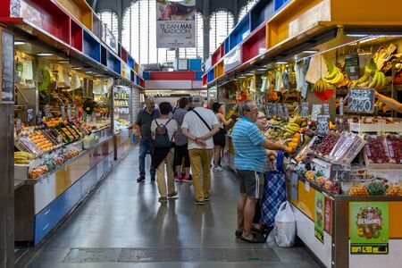 Malaga, Spain - May 24, 2019: People at fruit and vegetable stalls inside the famous Atarazanas Market.