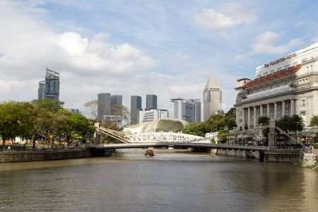 Singapore, Singapore - February 31, 2015: The Cavenagh Bridge and the Fullerton Hotel with the Durian building in the background.