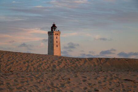Lokken, Denmark - July 15, 2019: Rubjerg Knude Lighthouse and sand dunes during sunset time.