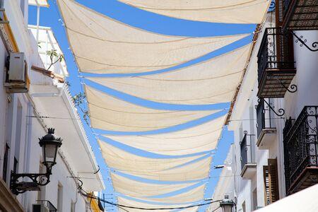 Nerja, Spagna - 28 maggio 2019: Il parasole bianco naviga nelle affascinanti strade di Nerja.