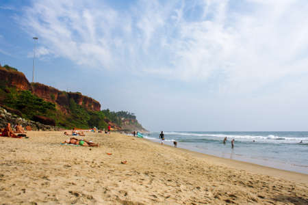 Varkala, India - February 1, 2011: People relaxing on the sand beach