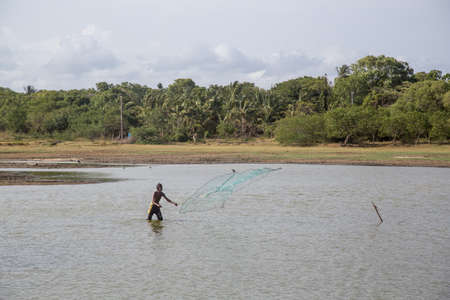 Sri Lankan man throwing fishing net