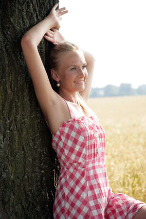 Young woman leaning against a tree photo