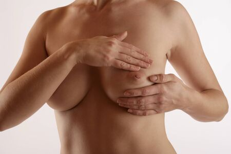 cancer screening: Young woman scans her breast for Cancer