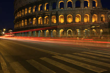 Light trails from traffic passing the colosseum at night