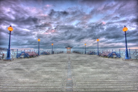 Winter skies over the Pier in Swanage bay in HDR photo
