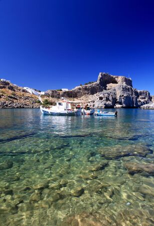 Emerald water at beautiful St Pauls Bay shadowed by the temple and castle ruins at Lindos