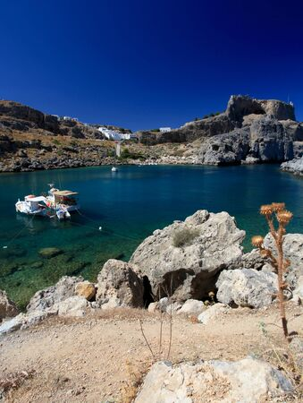 shadowed: Beautiful St Pauls Bay shadowed by the temple and castle ruins at Lindos  Stock Photo