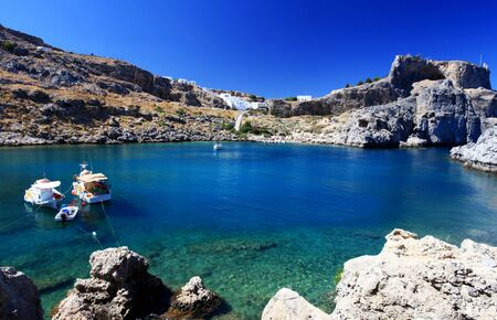 lindos: Beautiful St Pauls Bay shadowed by the temple and castle ruins at Lindos  Stock Photo
