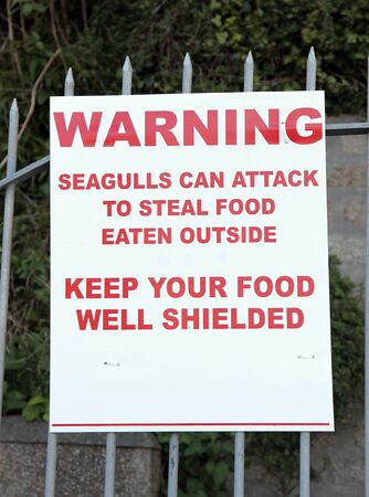 Seagul warning sign attached to a railing Banco de Imagens