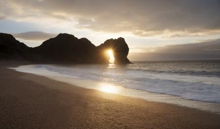 durdle door: Sunset on Durdle Door Beach in Dorset England Stock Photo