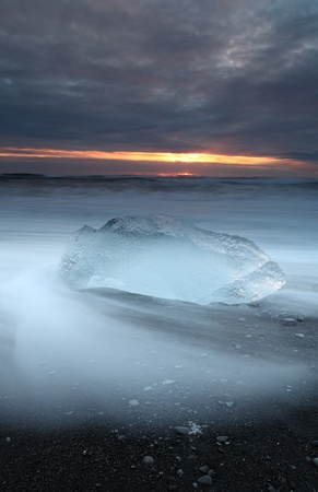 Ice on vocanic black sand iceland beach at sunset photo