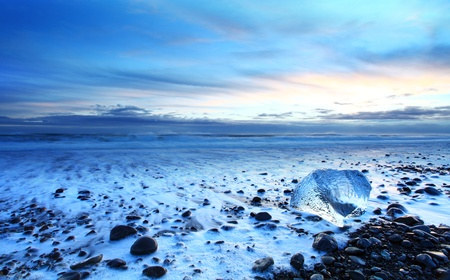 Iceburg on vocanic black sand beach at sunset in south Iceland photo