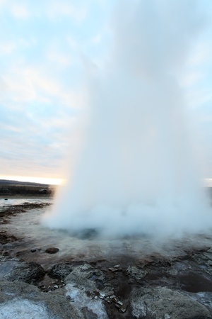 Strokkur Geyser in Iceland erupting at sunset in winter photo