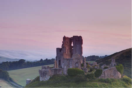 Oink sunset over Corfe Castle in Dorset photo