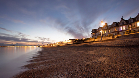 nightime: Nightime seascape in dorset with houses over looking the seafront at sunset almost dusk Stock Photo