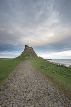 stargazing: Dawn breaks over Lindisfarne Castle on Holy Island Northumberland with the stars and Milky Way still overhead in the fading night sky. Editorial