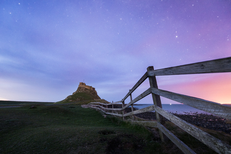 boarders: Dawn breaks over Lindisfarne Castle on Holy Island Northumberland with the stars and Milky Way still overhead in the fading night sky. Editorial