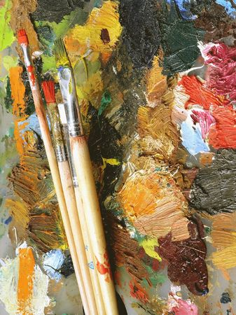 artist's stained palette and four different brushes