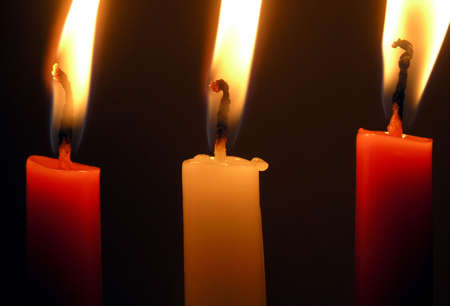 solemnity: three burning candles: two red and a white one