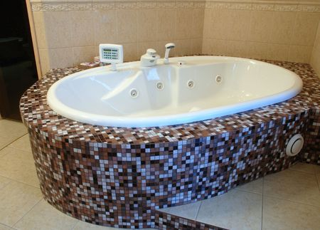 bathroom: jacuzzi layed with brown variegated mosaics